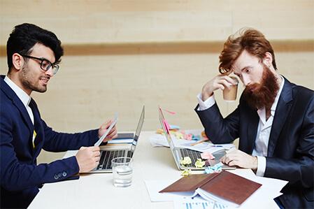 Aktuelles-Clean-Desk-Policy-zwei-Maenner-an-unterschiedlich-sauberen-Arbeitsplaetzen